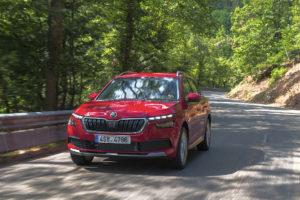 Un Skoda Kamiq rojo circulando por una carretera de bosque