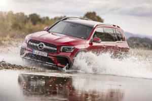 Un Mercedes - Benz GLB rojo cruzando un charco de agua