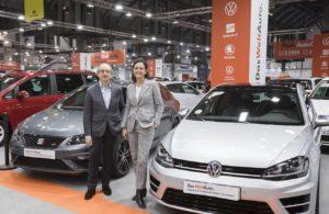Dos representantes de Das Weltauto con dos de sus vehículos de ocasión.
