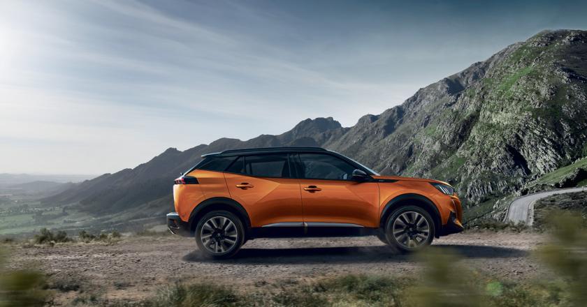 El nuevo SUV de Peugeot de color naranja en una carretera de montaña