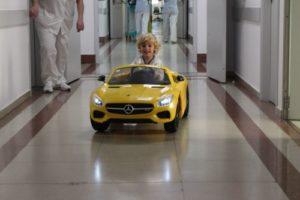 Un paciente conduciendo el vehículo eléctrico que lo llevará a quirófano