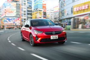 Un Opel Corsa rojo circulando por una calle de Japón